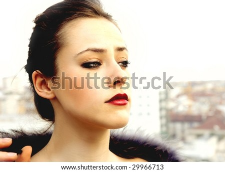 portrait of a rich beautiful woman with fur on the top of a building - stock photo