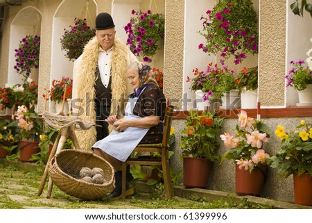 Portrait of a romanian traditional very old couple on country side. Focus on the basket balls. See more images with them. - stock photo