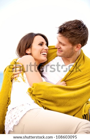 Portrait of a romantic couple on the beach wrapped in blanket looking at each other - stock photo