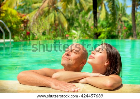 Portrait of a romantic couple with closed eyes enjoying sun light, tanning in a swimming pool, spending honeymoon on a tropical beach resort, happy summer vacation on Bali, Indonesia