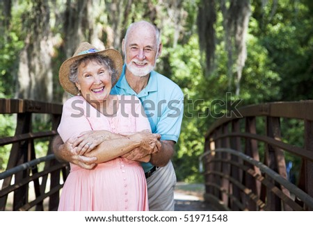 Portrait of a romantic senior couple on a bridge with Spanish Moss hanging overhead.