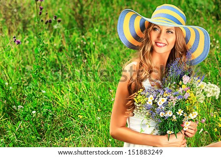 Portrait of a romantic smiling young woman with a bouquet of wild flowers outdoors. - stock photo