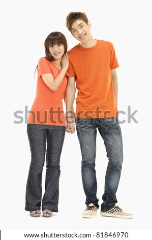 Portrait of a romantic young couple standing together over - stock photo