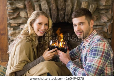 Portrait of a romantic young couple toasting wineglasses in front of lit fireplace