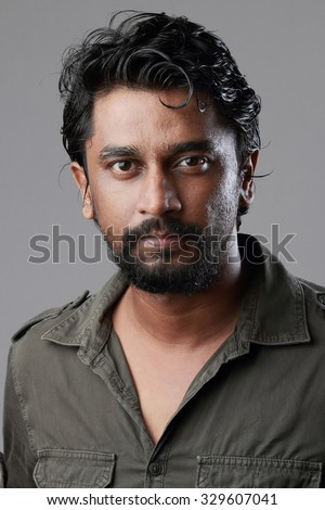 Portrait of a rough looking Indian young man with beard.With harsh light and shadow treatment. - stock photo