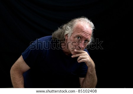 Portrait of a rugged looking man turned towards the viewer and looking thoughtful or judging with his hand to his mouth. - stock photo