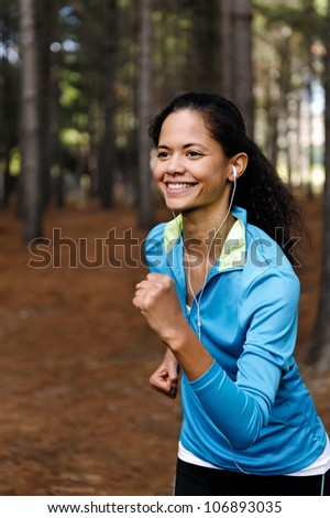 Portrait of a runner listening to music on headphones while running outdoors in a forest. healthy wellness fitness lifestyle. - stock photo