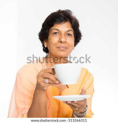 Portrait of a 50s Indian mature woman drinking coffee at home. Indoor senior people living lifestyle. - stock photo