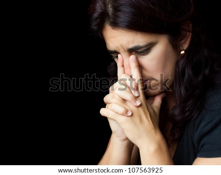 Portrait of a sad and stressed hispanic woman with a thoughtful expression isolated on black - stock photo