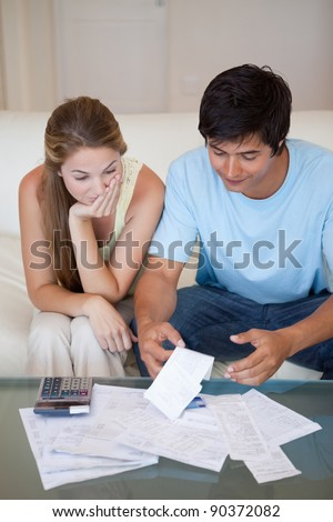 Portrait of a sad couple looking at their bills in their living room - stock photo