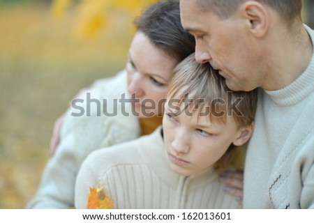 Portrait of a sad family of three on the nature - stock photo
