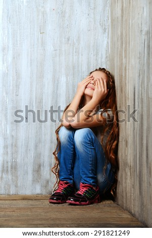 Portrait of a sad girl child sitting in the corner of the room. Loneliness, depression. Awkward age. - stock photo