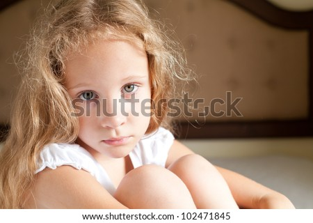 portrait of a sad girl sitting on a bed - stock photo