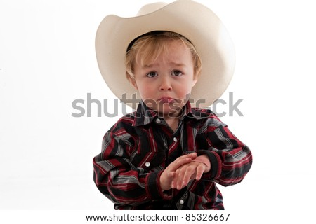 Portrait of a sad little boy in a cowboy hat. He is frowning and holding one hand in his other.