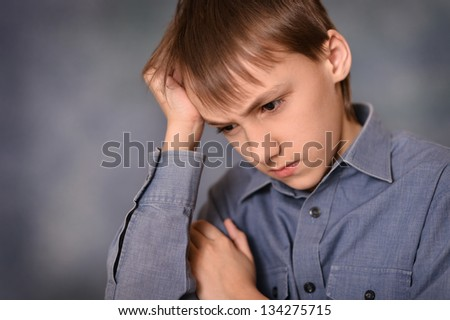 portrait of a sad little boy over a gray background - stock photo