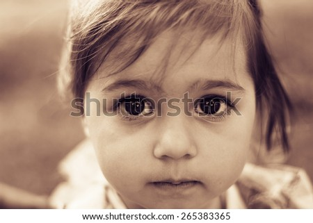Portrait of a sad little girl close-up. Toned - stock photo