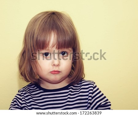 Portrait of a sad little girl on a yellow background