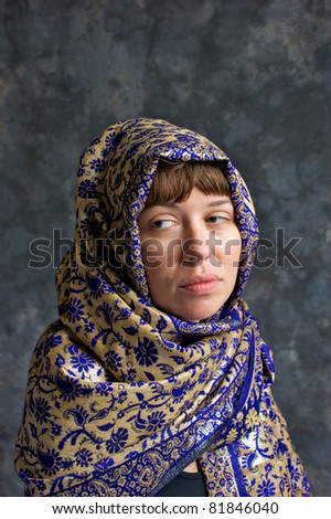 Portrait of a sad looking woman wrapped in a shawl and looking out the corner of her eyes. - stock photo