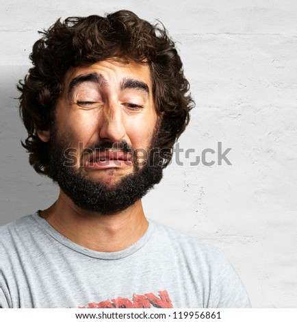 Portrait Of A Sad Man against a concrete wall - stock photo