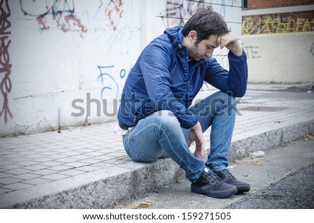 portrait of a sad man in a urban street - stock photo