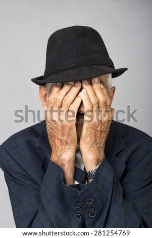 Portrait of a sad old man covering his face with hands over gray background - stock photo