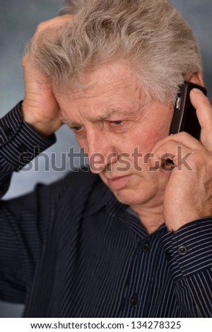 portrait of a sad older man calling on a gray background