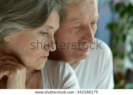 Portrait of a sad senior couple at home - stock photo