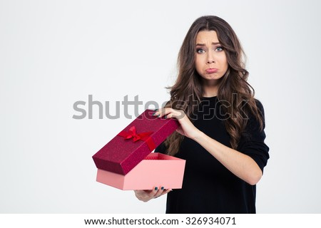 Portrait of a sad woman standing with opened gift box isolated on a white background and looking at camera - stock photo