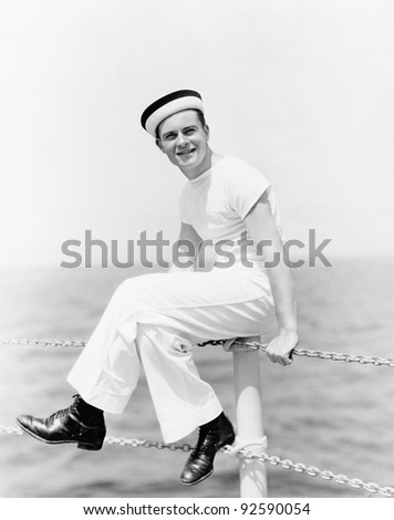 Portrait of a sailor sitting on the pole of a boat and smiling - stock photo