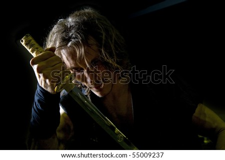 portrait of a samurai on a dark background - stock photo