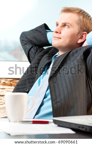 Portrait of a satisfied young businessman resting - stock photo