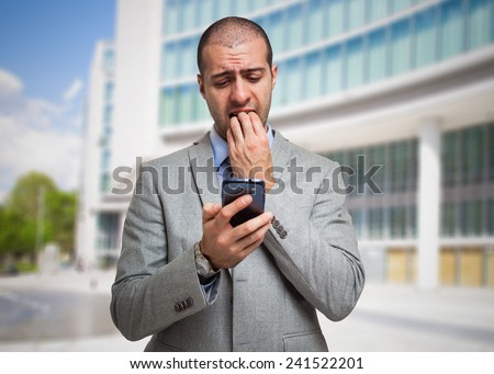 Portrait of a scared man looking at his mobile phone