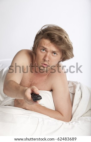Portrait of a scared young man lying in bed watching horror movies. Studio shot. See more in my portfolio - stock photo