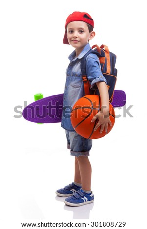 Portrait of a school boy holding a skateboard and a basketball on white background - stock photo