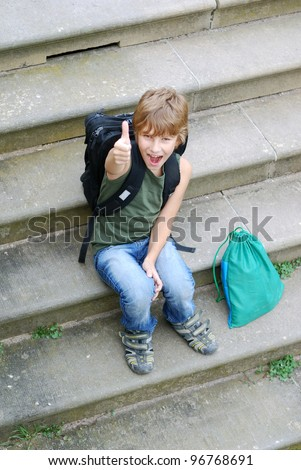 portrait of a school boy with thumbs up outdoors - stock photo
