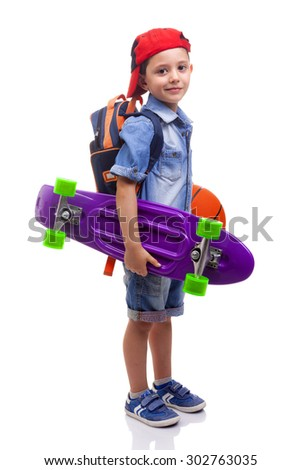 Portrait of a school kid holding a skateboard and a basketball on white background - stock photo