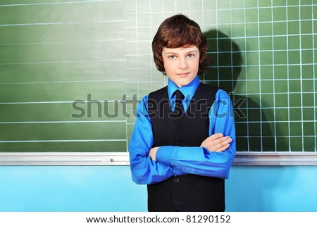 Portrait of a schoolboy in a classroom. - stock photo