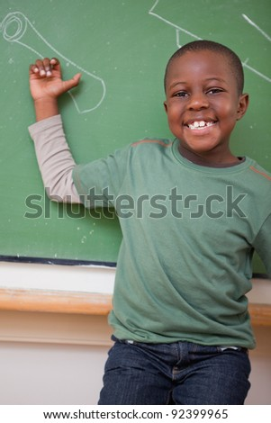 Portrait of a schoolboy showing something on a blackboard - stock photo