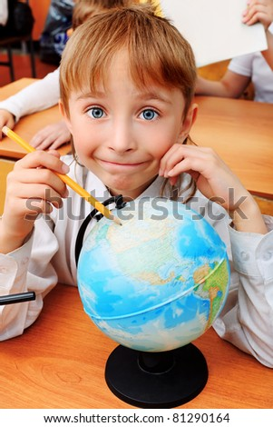 Portrait of a schoolboy with a globe in a classroom. - stock photo