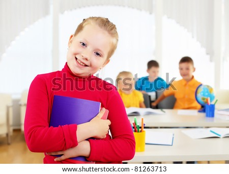 Portrait of a schoolgirl being in a classroom at school.