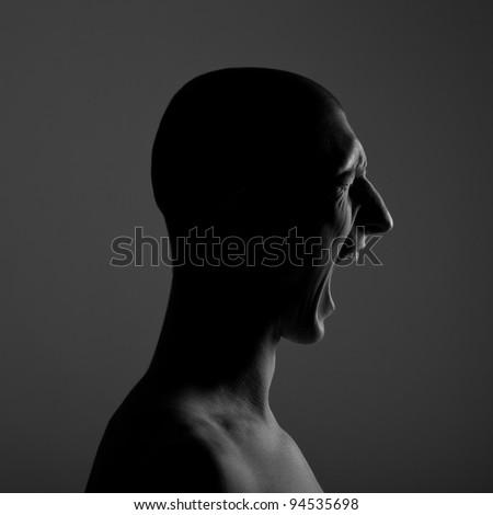 Portrait of a screaming man. Low-key lighting - stock photo