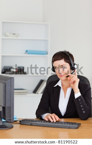 Portrait of a secretary calling with a headset in her office