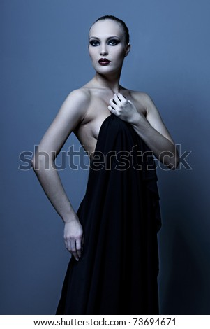 Portrait of a seductive glamorous lady in an elegant evening dress on blue background - stock photo