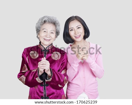 portrait of a senior asian mother and her adult daughter. - stock photo