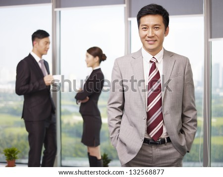 portrait of a senior business executive with his colleagues in the background.