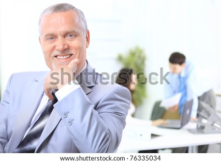 Portrait of a senior business man attending a conference with the rest of his business team - stock photo
