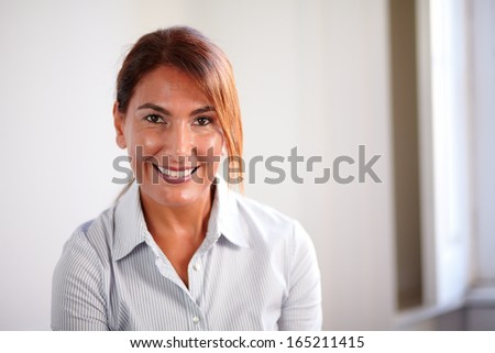 Portrait of a senior business woman smiling at you on closeup background - copyspace