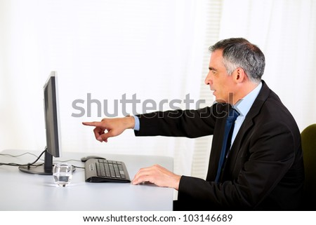 Portrait of a senior businessman pointing the computer screen at the office - stock photo