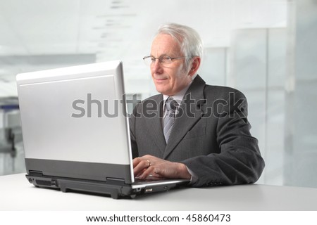 Portrait of a senior businessman siting in front of a laptop