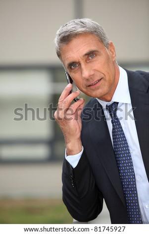 Portrait of a senior businessman talking on phone - stock photo